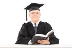 Uomo maturo in abito di graduazione che tiene un libro Immagine Stock