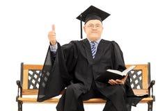 Uomo maturo in abito di graduazione sul banco che dà un pollice su Immagine Stock