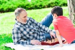 Uomo maturo allegro e suo il nipote che giocano scacchi immagine stock libera da diritti