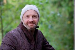 Uomo maturo bello che sorride in cappello caldo e rivestimento che esaminano macchina fotografica immagini stock libere da diritti