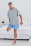 Uomo maturo che allunga la sua gamba Immagine Stock