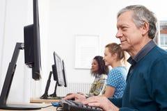 Uomo maturo che assiste alla classe del computer immagini stock libere da diritti