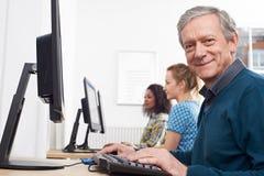 Uomo maturo che assiste alla classe del computer fotografie stock libere da diritti