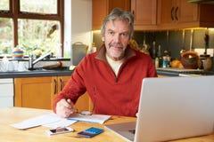 Uomo maturo che guarda a casa le finanze in cucina fotografia stock libera da diritti