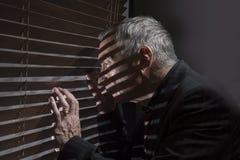 Uomo maturo che guarda da una finestra con i ciechi che gettano le ombre Fotografia Stock
