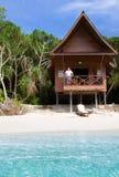 Uomo maturo che guarda l'oceano dal bungalow tropicale Fotografie Stock