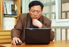 Uomo maturo che lavora ad un calcolatore Fotografie Stock Libere da Diritti