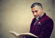 Uomo maturo che legge un vecchio libro che fa una pausa un muro di cemento all'aperto Immagini Stock