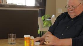 Uomo maturo che prende le pillole a casa stock footage
