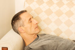 Uomo maturo che si trova sul sofà Fotografia Stock Libera da Diritti