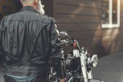 Uomo maturo che sta motocicletta vicina immagini stock libere da diritti