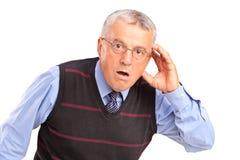 Uomo maturo che tiene la sua testa e che gesturing che cosa Fotografia Stock