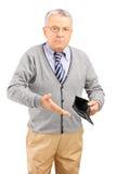 Uomo maturo che tiene un portafoglio vuoto Fotografia Stock Libera da Diritti