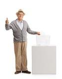 Uomo maturo che vota e che fa un pollice sul gesto Immagine Stock Libera da Diritti