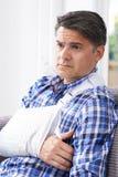 Uomo maturo con il braccio in imbracatura a casa immagini stock libere da diritti