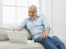 Uomo maturo con il computer portatile sul sofà Fotografia Stock