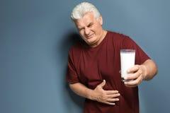 Uomo maturo con l'allergia della latteria che tiene vetro Fotografia Stock