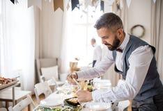 Uomo maturo con l'arco e maglia che mette una tavola per un partito dell'interno fotografia stock