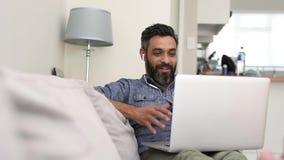 Uomo maturo con le cuffie durante la chiamata video d archivio