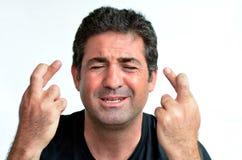 Uomo maturo con le dita attraversate che spera per la fortuna Fotografia Stock Libera da Diritti