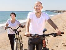 Uomo maturo e camminata femminile con le biciclette lungo il mare fotografia stock