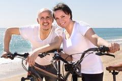 Uomo maturo e camminata femminile con le biciclette lungo il mare immagine stock