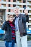 Uomo maturo e donna che rendono selfie con la chiave della casa disponibile Immagini Stock