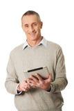 Uomo maturo felice che per mezzo della compressa digitale Fotografia Stock