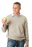 Uomo maturo felice con una mela Fotografie Stock Libere da Diritti