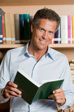 Uomo maturo in libreria Fotografia Stock