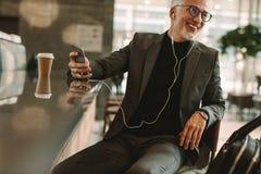 Uomo maturo a musica d'ascolto della caffetteria dal telefono Fotografia Stock