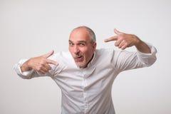 Uomo maturo positivo italiano in camicia bianca che indica se stesso con le dita di entrambe le mani, facenti smorfia divertente fotografie stock libere da diritti