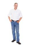 Uomo maturo sorridente che sta con le mani in tasche Fotografie Stock