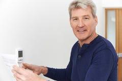 Uomo maturo sorridente con Bill Adjusting Central Heating Thermosta immagini stock
