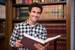 Uomo maturo sorridente in una biblioteca Immagine Stock