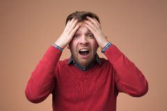 Uomo maturo triste che tiene la sua testa in mani e che grida fotografia stock