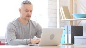 Uomo Medio Evo arrabbiato che lavora al computer portatile in ufficio Immagini Stock Libere da Diritti