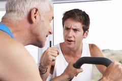 Uomo Medio Evo che è incoraggiato dall'istruttore personale In Gym Immagini Stock