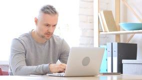Uomo Medio Evo che lavora al computer portatile in ufficio Fotografia Stock Libera da Diritti
