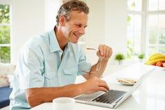 Uomo Medio Evo che per mezzo del computer portatile sopra la prima colazione Fotografia Stock