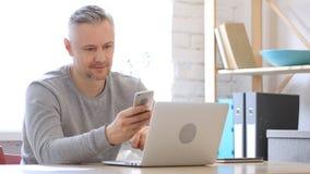 Uomo Medio Evo che usando Smartphone, invio di messaggi di testo Immagine Stock