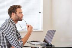 Uomo messo dietro il computer che esamina la distanza nel pensiero Fotografia Stock