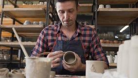 Uomo messo a fuoco caucasico che fa vaso ceramico nelle terraglie video d archivio
