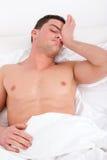 Uomo mezzo nudo che sveglia nella camera da letto e negli allungamenti a letto Immagini Stock Libere da Diritti