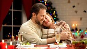 uomo Mezzo vecchio che bacia tenero moglie sulla notte di Natale, relazioni di amore in famiglia fotografia stock