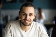 Uomo millenario sorridente che esamina macchina fotografica in caffè, portr di colpo in testa Fotografia Stock Libera da Diritti