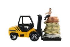 Uomo miniatura che si siede su un mucchio di euro monete su un truc del carrello elevatore Fotografia Stock