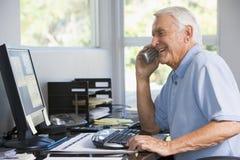 Uomo in Ministero degli Interni sul telefono per mezzo del calcolatore Immagini Stock Libere da Diritti