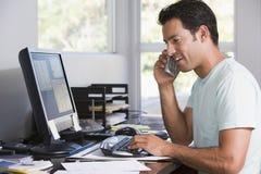 Uomo in Ministero degli Interni sul telefono per mezzo del calcolatore fotografie stock libere da diritti