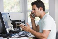 Uomo in Ministero degli Interni sul telefono per mezzo del calcolatore fotografia stock